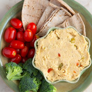 Green Olive Hummus on a platter with Grape Tomatoes, Broccoli Florets, and Pita Bread