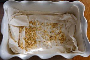 Layering phyllo sheets and nut mixture
