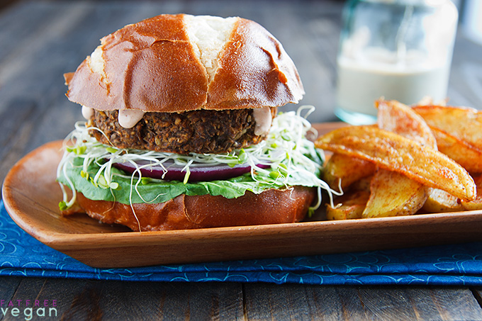 Savory Mushroom-Lentil Burgers on a wooden tray with oven-baked fries