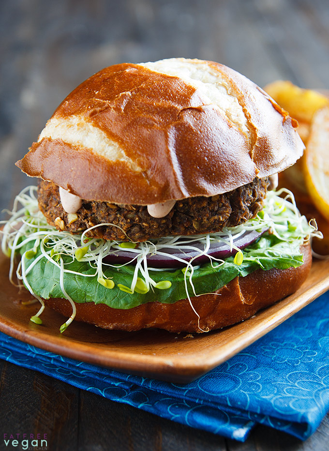Lentil-Mushroom Burgers on a wooden platter with oven-baked fries