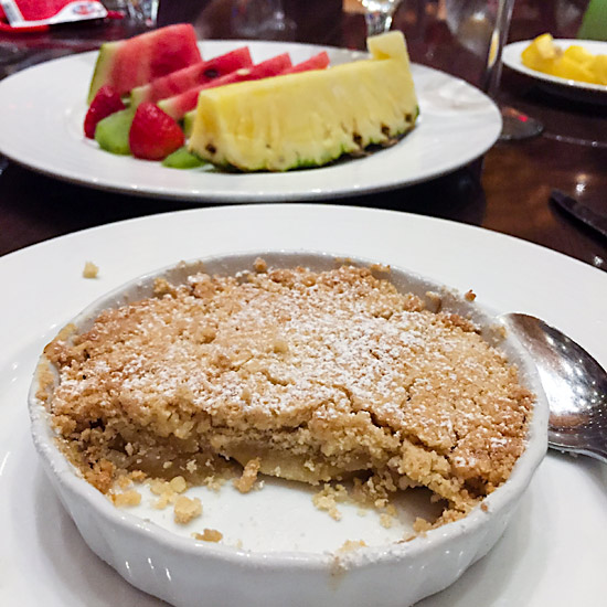 Two desserts: A plate of fruit and a apple cobbler