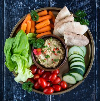 Baba Ganoush on a platter with pita bread., baby carrots, lettuce, tomatoes, and sliced cucumber