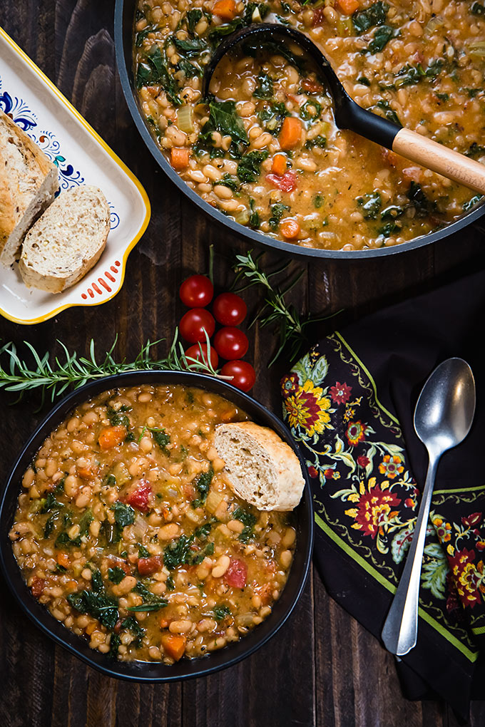 Vegan Tuscan White Bean Soup in a bowl with bread and in a pot
